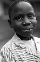 Portrait of a young student. Rehaboth Integrated School.  Most of the 130 plus children that attend this school are orphans due to HIV/AIDS. Uganda has an estimated 1.5 million people infected with HIV/AIDS and contains over 1 million orphans. Bugembe, Jinja District, Uganda, Africa. June 2004 © Stephen Blake Farrington