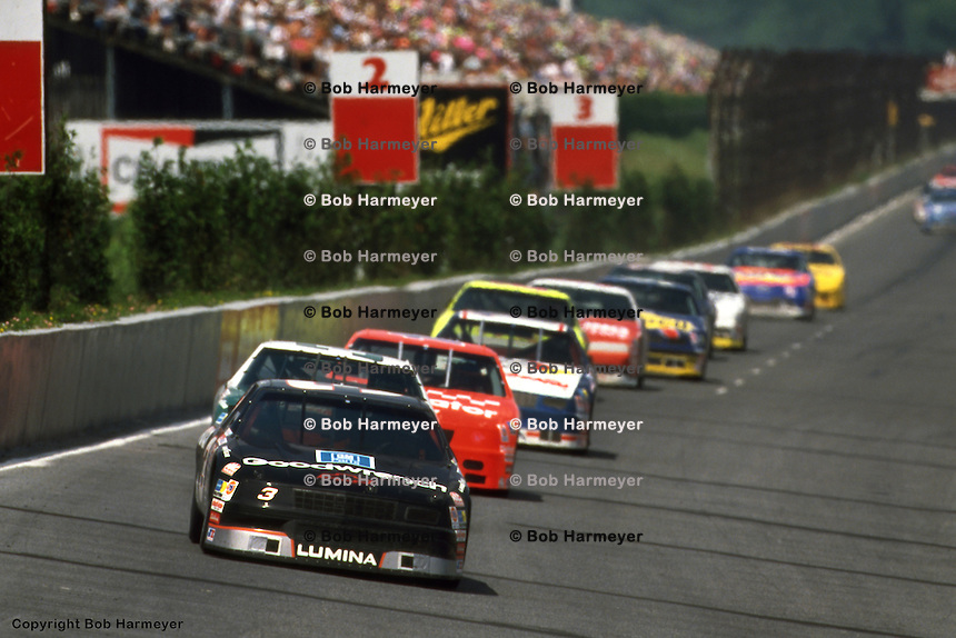 LONG POND, PA - JUNE 14: Dale Earnhardt leads a group of cars into Turn 1 during the Champion Spark Plug 500 on June 14, 1992, at the Pocono International Raceway near Long Pond, Pennsylvania.