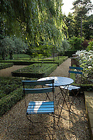 Turquoise garden table and chairs in late afternoon dappled sunlight underneath a willow tree