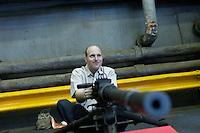 New York, USA. 22nd May, 2014. A man sits on a machine gun during the Fleet Week at pier 92 in Manhattan, New York.  Kena Betancur/VIEWpress