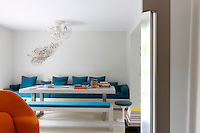 The dining room is furnished with a banquette designed by architect Karine Lewkowicz and upholstered in turquoise fabric which flanks a concrete table