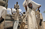 Men unload food from the World Food Program in the Habile Camp for internally displaced persons outside the village of Koukou Angarana, Chad. Some 28,000 people live in precarious conditions in this camp. More than 180,000 residents of eastern Chad have been displaced by violence spilling over from neighboring Darfur, inter-ethnic conflict, and fighting between rebels and the Chadian government.