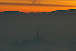 San Francisco's Coit Tower and the Bay Bridge lineup together as the sun lights up the a east bay hills in Oakland, California.