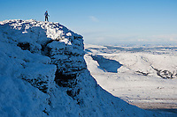 Hiker enjoys scenic winter view from summit of Corn Du, Brecon Beacons national park, Wales