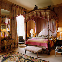 This Victorian four-poster bed is hung with red and white tasselled brown chintz