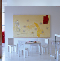 Children's chairs and table designed by Bonnie Young sit beneath a large canvas in one corner of the kitchen