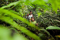 Seven year old Dayume Ganquimi walks through the jungle with her aunt, Hewenka Tega, carrying home some fish her uncle speared in the Shiripuno River. They live in the Waorani (Huaroni) community of Noneno.