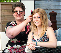 BNPS.co.uk (01202 558833)<br /> Pic: TomWren/BNPS<br /> <br /> Lauren Green (17) has her new wig brushed by her mum Jo.<br /> <br /> Hair today, hers tomorrow!<br /> <br /> A doting mum has 'baldly' gone where no mother has gone before - shaving her head to make her alopecia-suffering daughter a special wig.<br /> <br /> Jo Green, 41, grew her hair for three years so she would have enough to make daughter Lauren, 17, a hair-raising gift to say thank you for everything the teenager has done to help her.<br /> <br /> Lauren was just eight years old when her hair started falling out and she went from having a full head of long, blonde locks to being completely bald in just three days.<br /> <br /> Despite this Jo says Lauren has never complained and has always tried to help others.