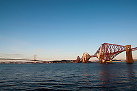 A (close to) sunset photo of the Forth Rail Bridge, and the Forth Road Bridge, crossing the Firth of Forth between Edinburgh and Fife. Snow can be seen on the mountains in Fife, across the Forth..The Forth Bridge is an instantly recognisable landmark associated with Scotland and Edinburgh in particular and might be nominated as one of the UNESCO World Heritage Sites in Scotland.