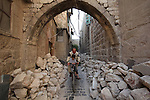 A Syrian man rides a bicycle on the rubble of buildings which destroyed by Syrian government forces in the northern Syrian city of Aleppo, on August 25, 2015. Photo by Ameer al-Halbi