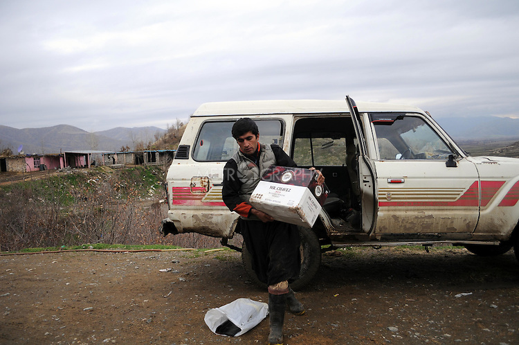 BASHMAKH, IRAQ:  An Iranian Kurdish smuggler prepares to load alcohol onto his horses to take into Iran...Iranian Kurdish smugglers traffic petrol from Iran into Iraq and alcohol from Iraq into Iran.  On foot, a smuggler can look to make around $10 per trip whereas with a horse a smuggler can make $100.  The routes are very dangerous with the risk of stepping on land mines or  being shot by the Iranian military..Photo by Kamaran Najm/Metrography