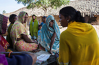 Shanti Adivasi (in yellow saree), 52, speaks with a group of illiterate women, as they wait to attend a group reading of this week's newspapers in their village in Manikpur, Chitrakoot, Uttar Pradesh, India on 6th December 2012. Shanti used to be a wood gatherer, working with her parents since she was 3, and later carrying up to 100 kg of wood walking 12km from the dry jungle hills to her home to repack the wood which sold for 3 rupees per kg. After learning to read and write in an 8 month welfare course, at age 32, she became a reporter, joining Khabar Lahariya newspaper since its establishment in 2002, and making about 9000 rupees per month, supporting her family of 14 as the sole breadwinner. Photo by Suzanne Lee for Marie Claire France.