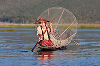 Myanmar, Burma.  Young Burmese Woman Looking for a Place to Set her Fishing Net.  Inle Lake, Shan State.  She is wearing thanaka paste on her cheeks, a Burmese cosmetic sunscreen.