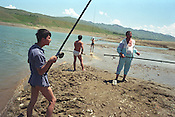 Men fishing to supplement their incomes at the Papan reservoir, near the city of Osh, once one of the great cities of the Silk Road and of Central Asia, and the second biggest city in the country, situated in the unstable Ferghana valley which is now becoming a hotbed if Islamic Fundamentalism. Osh, Kyrgyzstan.