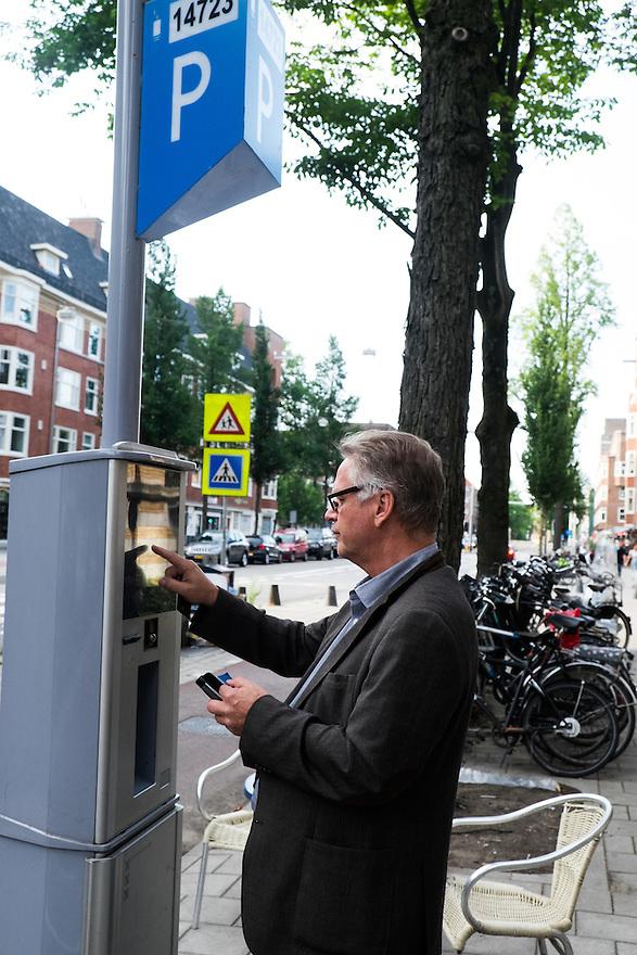 Nederland, Amsterdam, 16 juli 2015<br /> Man koopt een parkeerkaartje in Amsterdam Zuid. Hij moet zijn kenteken invoeren en met pinpas betalen. <br /> <br /> Foto: Michiel Wijnbergh
