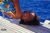 Young girl on vacation on a sailboat, Tahiti, French Polynesia