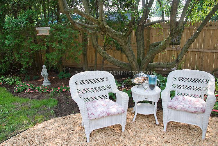 backyard pebble circular patio with wicker furniture