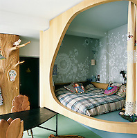 The apartment has a raised bedroom screened from the dining area by a curved wood panel turning the sleeping area into a separate pod