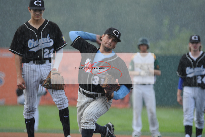 In a downpour, relief pitcher Sam Hanson warms up as Charlie Bucolo and Cody Curfmanlook on.