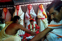 INDIA (West Bengal - Calcutta)  2006, Priests worship a  pre adolescent girl child as a part of Durga Puja Festival at a pandal decorated with Bengali women figures. This ritual is called Kumari Puja (Kumari - Pre adolescent girl child, puja - worship).  Durga Puja Festival is the biggest festival among bengalies.  As Calcutta is the capital of West Bengal and cultural hub of  the bengali community Durga puja is held with the maximum pomp and vigour. Ritualistic worship, food, drink, new clothes, visiting friends and relatives places and merryment is a part of it. In this festival the hindus worship a ten handed godess riding on a lion armed wth all possible deadly ancient weapons along with her 4 children (Ganesha - God for sucess, Saraswati - Goddess for arts and education, Laxmi - Goddess of wealth and prosperity, Kartikeya - The god of manly hood and beauty). Durga is symbolised as the women power in Indian Mythology.  In Calcutta people from all the religions enjoy these four days of festival in the moth of October. Now the religious festival has become the biggest cultural extravagenza of Calcutta the cultural capital of India. Artistry and craftsmanship can be seen in different sizes and shapes in form of the idol, the interior decor and as well as the pandals erected on the streets, roads and  parks.- Arindam Mukherjee