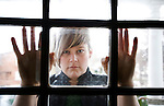 A blond woman wearing a classy green dress is seen through an old window in a retro house in Victoria, BC, British Columbia, Canada.