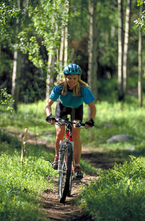 Woman mountain biking in forest in Rocky Mountains of Colorado. Colorado.