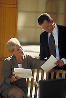 Man and woman discussing business; looking over documents. Normal view. Professionals. Lawyers.Businesswoman. Businessman. Denver Colorado USA.