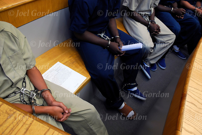 Juveniles in handcuffs and leg irons sitting in Juvenile Court waiting ...