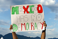 Political protestor holding up a sign the Mexico Fest 2012 celebrations on Sept. 8, 2012 in Vancouver, British Columbia, Canada. These celebrations commemorated 202 years of Mexican Independence.