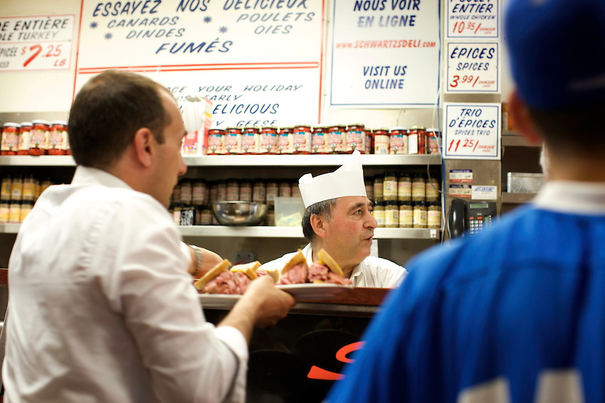 MONTREAL, Quebec, Canada - June 10, 2012: A counterman serves Viande Fumee (smoked meat), at Schwartz's in the Plateau district. CREDIT: Clay Williams.<br /> <br /> &copy; Clay Williams / http://claywilliamsphoto.com