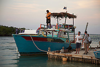 Belize, Central America - Rasta man's tour boat tied up at the Lazy Lizard bar on the Caye Caulker waterfront.