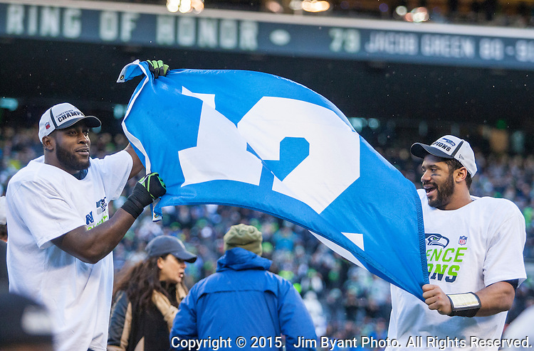 Seattle Seahawks strong safety Kam Chancellor, left, and quarterback Russell Wilson, right, wave the 12th man Flag after their 28-22 overtime in the NFC Championship game against the  Green Bay Packers at CenturyLink Field in Seattle, Washington on January 18, 2015.  The Seattle Seahawks beat the Green Bay Packers in overtime 28-22 for the NFC Championship Seattle.  ©2015. Photo by Jim Bryant, All Rights Reserved.
