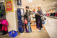 Customers use a price scanner at the soon to be closing Sears store in Rego Park in the New York borough of the Queens on Saturday, February 18, 2017. Sears Holdings has deemed the store unprofitable and it will be closing sometime in April. The store is one of the 42 stores they will close in the spring. Sears is also closing 108 Kmart stores. (© Richard B. Levine)