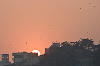 Kite flying is extremely popular.  In this one small area, many kites can be seen against the orange sky. On this afternoon there were thousands of kites flying over Varanasi. (Photo by Matt Considine - Images of Asia Collection)