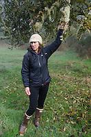 SV Maple Leaf Naturalist Jolie Shea shows off epiphyte plants, Prevost Island, Gulf Islands National Park Preserve, British Columbia, Canada