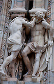 Milan, Italy, Duomo Cathedral. Statues of two men supporting pedestals.
