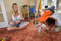 A woman sits crosslegged on the carpet of her living room floor breastfeeding her baby boy whilst her husand plays with their older boy. <br /> <br /> 09/07/2011<br /> Hampshire, England, UK