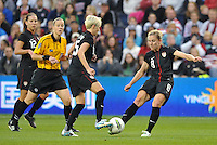 USWNT midfielders Megan Rapinoe (15) and Amy Rodriguez (8) go for the same ball.