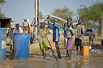 Children enjoy water from a newly drilled well in an internally displaced persons camp in Aweng, South Sudan. Families started arriving here shortly after fighting broke out in December 2013, and new families continued to arrive in March 2014 as fighting continued. The ACT Alliance is providing the displaced families and the host communities affected by their presence with a variety of support, including the drilling of this and other new wells.