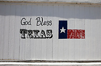 "View of a iconic ""God Bless Texas"" mural with Texas Flag painted on the side of a building in the Texas Hill Country."