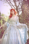 A pretty young woman standing outdoors holding a book wearing white victorian party dress stares off into the distance