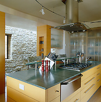 The grey stone worktops in the kitchen echo the colour of the massive walls in the corridor
