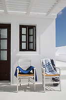A pair of chairs at the entrance to this Greek villa have been placed in the shade of a rustic canopy on the terrace