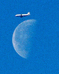 An airplance seem to be pasting up the moon over San Francisco, California.