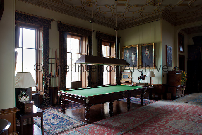 Billiard cues line the walls between the floor-to ceiling windows of the billiard room/inner hall