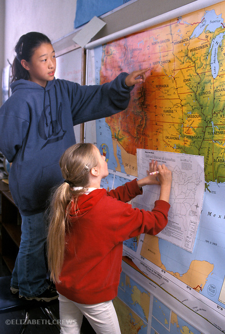 Berkeley CA 5th grade girls using classroom map to work on their U.S. geography project