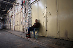 A Palestinian man sits a closed shops during a general strike in support of Palestinian prisoners on hunger strike in Israeli jails, in the old market of the West Bank city of Nablus April 27, 2017. Photo by Ayman Ameen