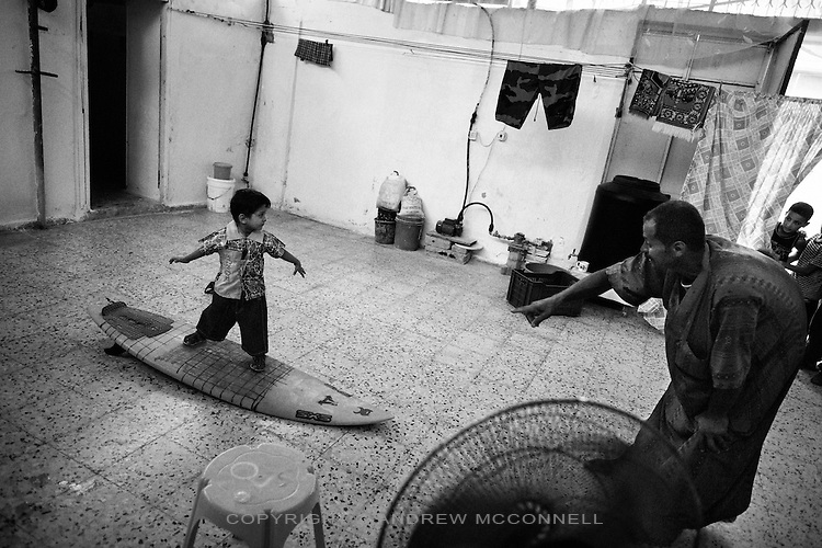 Mohammed Abu Jayab teaches his son to surf, at his home in Shati Refugee Camp, in the Gaza Strip. Abu Jayab is the leader of a surf group in Gaza and one of the pioneers of the sport in the coastal enclave.