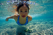 A young girl with eyes open swims underwater in the clear, blue shallow water of the ocean on the Big Island of Hawaii