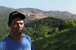 Pedro Ignacio Guzman, resident of the community of La Cerca, stands on the Cerro del Chivo peak as Barrick and Goldcorp's Pueblo Viejo gold mine lays North behind him. Cotuí, Sánchez Ramírez, Dominican Republic. April 2012.